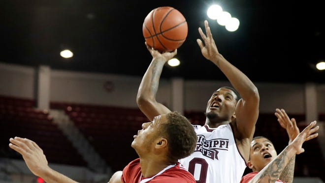 Mississippi State guard Nick Weatherspoon (0) attempts a shot between two Arkansas defenders during the first half of their NCAA college basketball game in Starkville, Miss., Tuesday, Jan. 2, 2018. (AP Photo by Rogelio V. Solis)