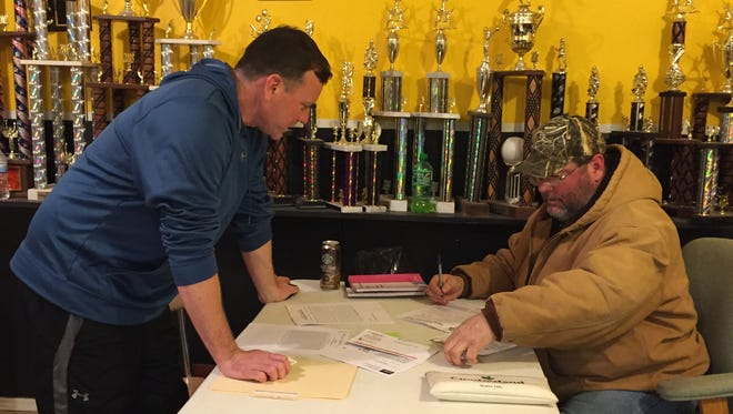 Brett Lerhman, left, signs up his son for Little League at the Athletic Association of Stewart County as Ricky Robinson helps with the paperwork. Lehrman also volunteered as a coach.