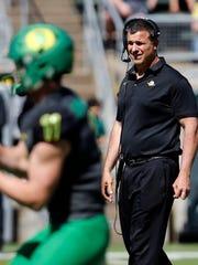 Oregon head coach Mario Cristobal, right, watches quarterback