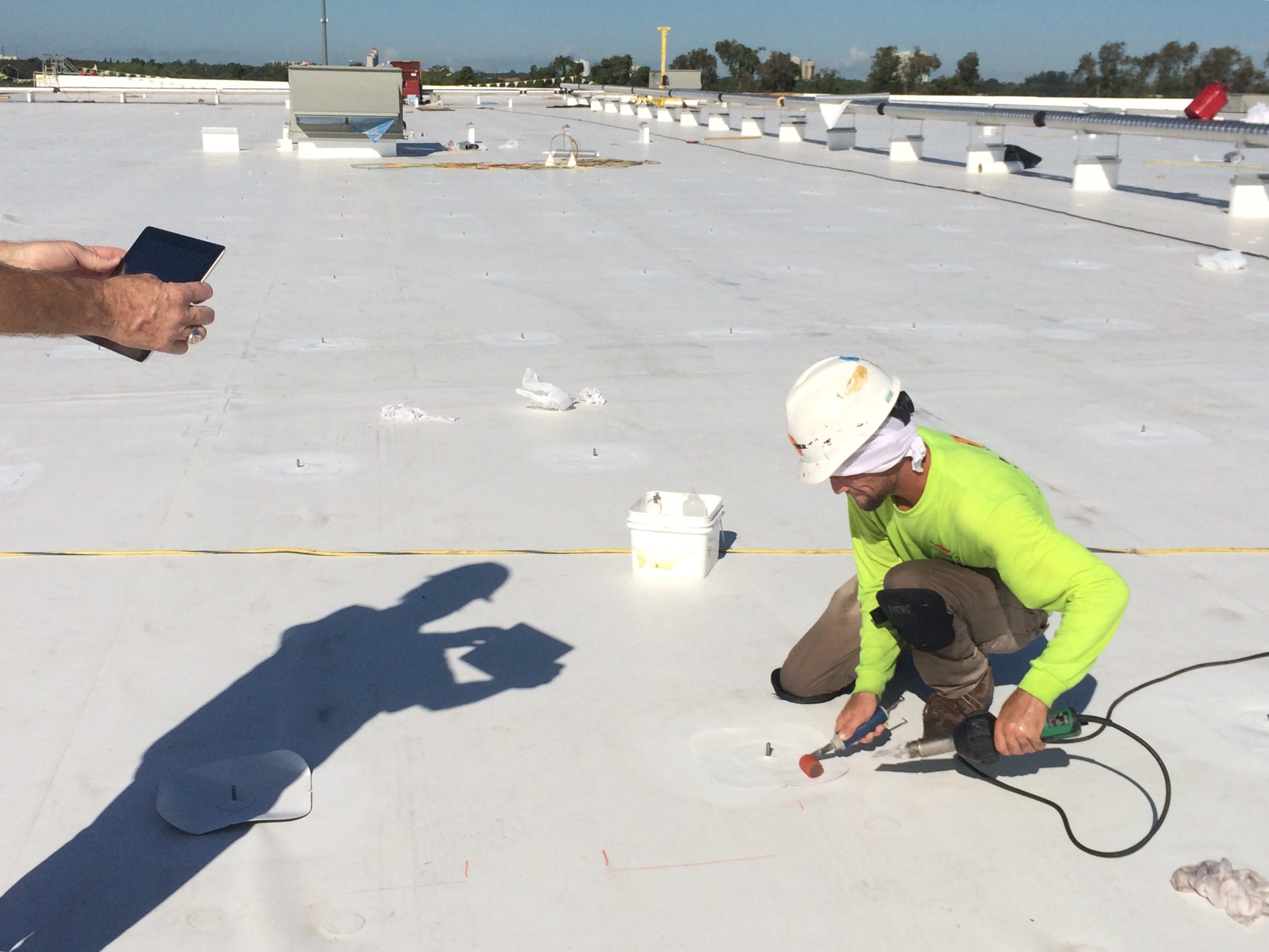 Scott McIntyre, CEO Of Tampa Bay Based Solar Energy Management, Takes An  IPad Shot Of A Crowther Roofing Worker Installing A Fastener By Heat  Welding It To ...
