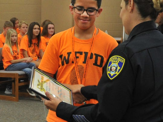 Wichita Falls Junior Citizens Police Academy student Raymond Arredondo receives his graduation certificate Friday morning during a ceremony honoring the students of the first 2017 class. WFPD Public information officer Jeff Hughes said the next class is in July but it is already booked.