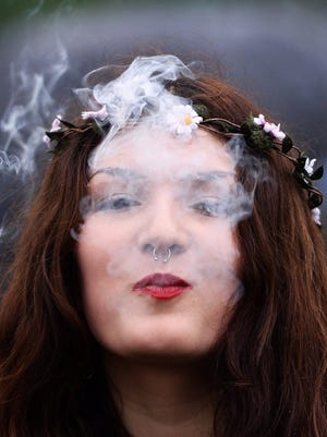 A young woman smokes cannabis during a demonstration calling for cannabis to be legalized at a 420 Day event in Hyde Park in London, Britain.