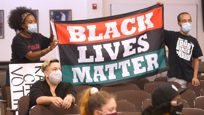 Sierra Mason and Steven Hall hold up a Black Lives Matter sign during their meeting Wednesday with Canton City Council.