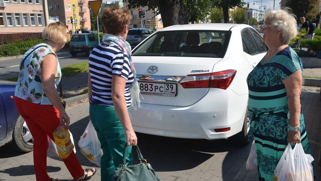 (FILES) This file photo taken on August 29, 2016 shows Russian shoppers carrying bags at a supermarket in Braniewo, a town near Poland's border with the Russian exclave of Kaliningrad. Poland adopted legislation on November 24, 2017 that will ban most Sunday trading by 2020, with opinion surveys showing that consumers have mixed feelings about the move in the heavily Catholic EU state.