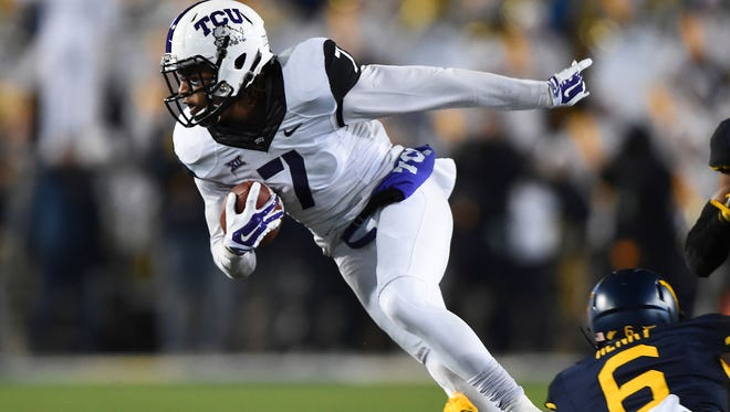 TCU wide receiver Kolby Listenbee tries to escape a tackle from a West Virginia defender during a game in 2014.