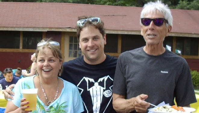 John M. Dunn, right, who goes by the name Mike after his middle name, is seen with his wife, Sue, left, and son Blaine in this 2013 photo. Dunn remains in critical condition after a bicycle accident left him with skull fractures and other trauma.