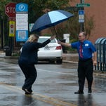 Keven Vaughn, right offers his umbrella to co-worker, Lisa Scruggs, left, during the onset of November showers in downtown Pensacola.