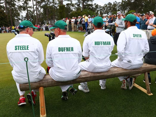 Caddies on the putting green during a practice round