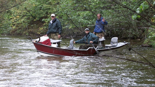 Brett Sundeck rows his boat on the Pere Marquette River while Alan Baxter, left, and Steve Yntema watch for pods of chinook salmon back in 2003.