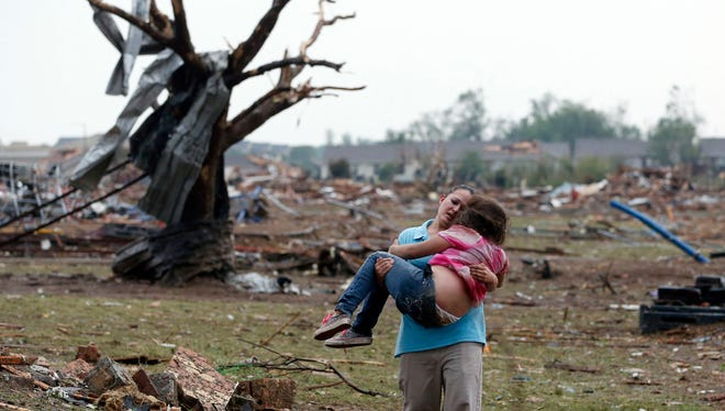 A woman carries a child through a field in Moore, Okla., on May 20, 2013, after a killer tornado ripped across the city.