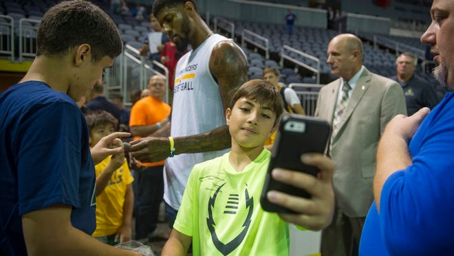 Jad Takieddin, 13, of Evansville, takes a selfie with Indiana Pacers forward Paul George (13) in the background a preseason game between the Indiana Pacers and the Milwaukee Bucks at the Ford Center in Evansville, Wednesday, Oct. 12, 2016.