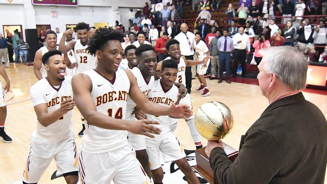Xavier Howard (14) and the rest of the Bobcats come out to accept the MACJC Gold Ball from Commissioner Jim Southward at A.B. Howard Gymnasium Thursday night.