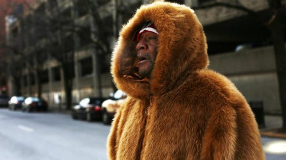 Leon Griffith crosses Market Street in downtown Louisville during the below freezing weather on Monday. January 6, 2013