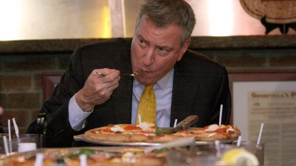 New York City Mayor Bill de Blasio eats pizza with a fork in 2014 at Goodfellas Pizza in Staten Island . That's a no-no for many New Yorkers, who are very opinionated when it comes to proper pizza-eating technique.