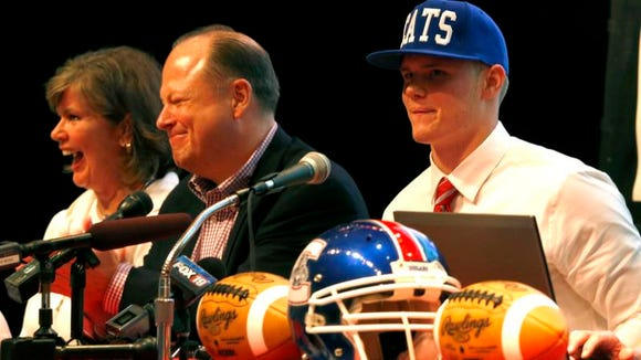 Conner quarterback Drew Barker, right, smiles after putting on a UK cap when announcing he had selected the Wildcats last May.