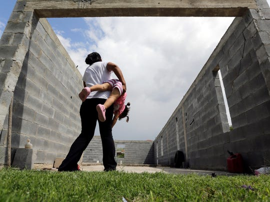 In this Sept. 16, 2015, photo, a woman in Sullivan City, Texas, who said she entered the country illegally, plays with her daughter who was born in the United States, but was denied a birth certificate. Texas has for seven years said it won't accept Mexican identification cards when issuing birth certificates for children of people in the United States illegally. But it doesn't appear to have stepped up enforcement until recently, amid mounting political pressure to get tougher on immigration, documents obtained by The Associated Press show.
