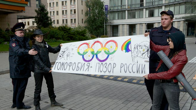 "In this Sept. 25, 2013 file photo, police officers detain two gay rights activists holding a poster reading ""Homophobia is Russia's Disgrace"" during a protest outside the Sochi 2014 Winter Olympic Games organizing committee office, in downtown Moscow, Russia."