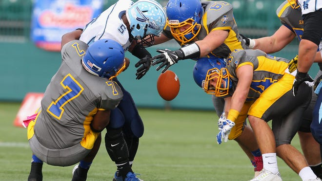 Indian River quarterback Densel Barnes (5) loses the ball as he is sacked by Irondequoit's Jamel Young (7), Isaiah Luciano (61) and John Lombardi (44).