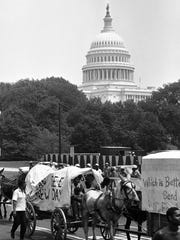 People walk alongside two wagons of the mule train of the Poor People's Campaign as it makes its way down First Street N/W., past the U.S. Capitol in Washington  June 25, 1968. The mule train came into Washington on June 25 earlier in the day from its camp on the Virginia side of the Potomac River.