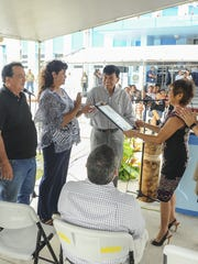 Francisco Santos, Port Authority of Guam board chairman, receives a legislative proclamation from Speaker Judith Won Pat during a flag raising ceremony at the Jose D. Leon Guerrero Commercial Port in Piti on Monday, Oct. 19.