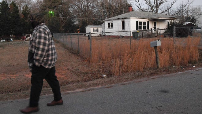 A man walks by a white home where another man died at 3504 Shawnee Avenue in Anderson on Wednesday night. Homeland Park fire responded to the fire in the South side of Anderson, getting help by volunteers from Starr fire station.
