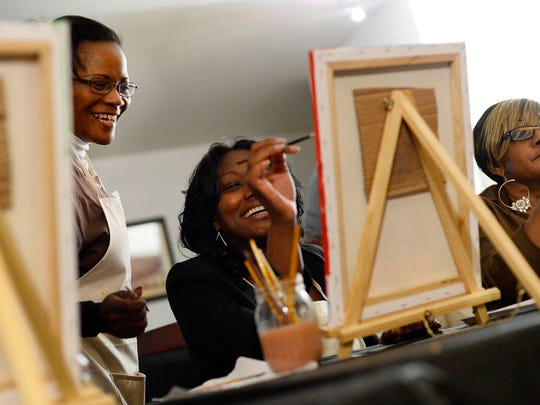 Artist Ophelia Chambliss, left, helps Kia Twyman of Coatsville during a sip and paint night put on by Inclusive Arts, a group dedicated to connecting different cultures through art.