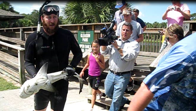 "Leo Cross carries ""Sushi"" the bull shark out of the Gleason Park pond last June in Indian Harbour Beach."