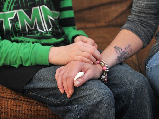 Kristen Shearer rests her hand on her son's knee, Kaleb, as she talks about her mother, Linda Perry.