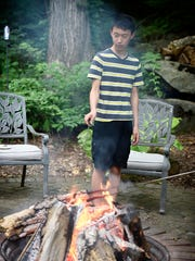 The Harnish family has already adopted six children, and now is adopting two more. Benjamin, 12, roast marshmellows in the backyard of their home.