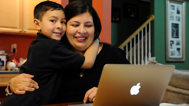 Marisela Martinez-Cola, right, a lawyer and a parent living in an Atlanta suburb with her husband Greg and their 7-year-old son, David, left, gets ready for a typical day Tuesday, Sept. 30, 2014, in Lawrenceville, Ga. Martinez-Cola sends her son to private school and has hired a tutor to improve his reading _ expenses made possible by her husband's salary as a regional buyer for Costco Wholesale.