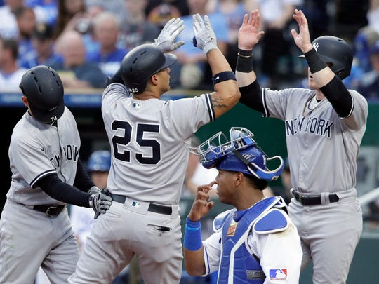 New York Yankees' Gleyber Torres (25) celebrates his three-run home run with teammates Ronald Torreyes, left, and Clint Frazier, right, next to Kansas City Royals catcher Salvador Perez (13) during the fourth inning at Kauffman Stadium in Kansas City, Mo., Saturday, May 19, 2018.