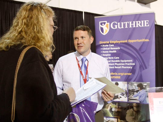 Guthrie representative Justin Shadduck speaks with a health care job seeker Tuesday at the Chemung-Schuyler-Steuben Workforce regional job fair at the Murray Athletic Center of Elmira College.