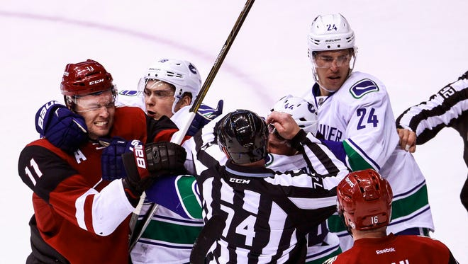 The Coyotes' Martin Hanzal (11) and the Canucks' Matt Bartkowski (44) throw punches in the third period of their game Wednesday.