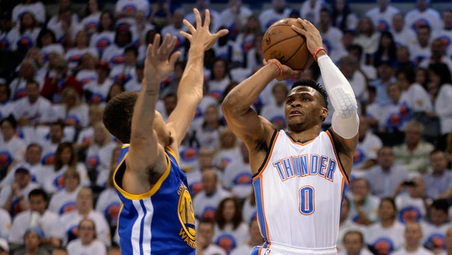 Thunder guard Russell Westbrook shoots as Warriors guard Stephen Curry defends during the first quarter.