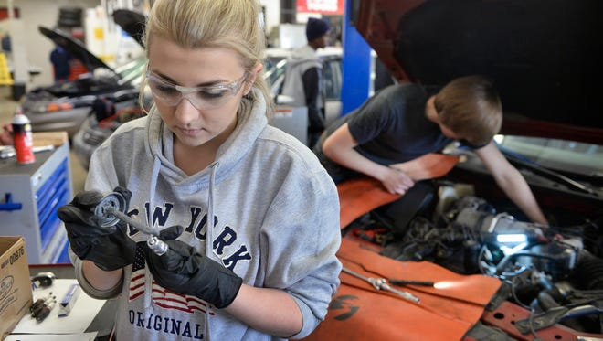 Sartell High School senior Brianna Hinnenkamp puts anti-sieze compound on a spark plug Friday, April 8, as she and a partner finish a tune-up in the automotive lab at Apollo High School. Hinnenkamp and fellow Sartell senior Gavin Oftedahl recently placed 12th in the National Automotive Technology Competition in New York City.