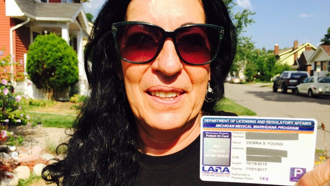 Deborah Young of Ferndale is a registered medical-marijuana user. She is holding her Michigan state issued card.