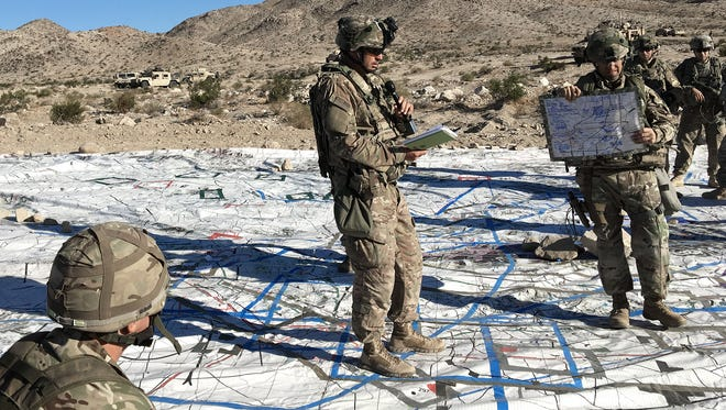 Leaders with 2nd Brigade plan an operation during their rotation at the National Training Center. Here, they use a giant map for an outdoor briefing.