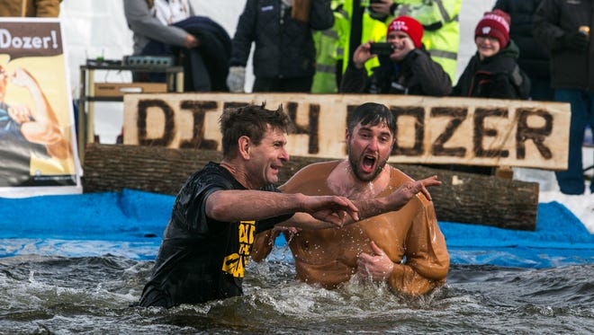 Bob Ripp and Brandon Asselin, both of whom traveled from out of state to participate, jump into frozen Lake Ripley during the Dip for Dozer scholarship fundraiser in Cambridge in February. Asselin was part of a group that flew in from Washington, and Ripp drove from Peoria, Ill., to join his daughter who was part of the Washington group.
