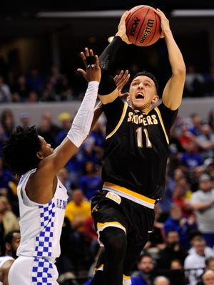 Wichita State Shockers guard Landry Shamet (11) shoots against Kentucky Wildcats guard De'Aaron Fox (0) during the second half in the second round of the 2017 NCAA Tournament at Bankers Life Fieldhouse.