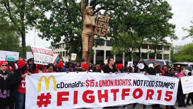 Demonstrators calling for $15-an-hour pay march near McDonald's headquarters in Oak Brook, Ill., on May 20.