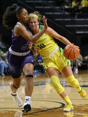 Oregon's Lexi Bando drives against Weber State's Shine Johnson during an NCAA college basketball game in Eugene, Ore., Saturday, Dec. 2, 2017.