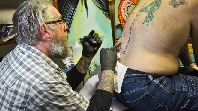 """Hula Moon Tattoo's """"Famous Gabe,"""" Gabriel Smith, works on a """"Star Wars"""" tattoo during the shop's """"May the Fourth be Tattooed"""" promotion on """"Star Wars"""" Day."""