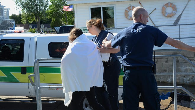 Door County EMTs lead kayaker, Danielle A. Petkunas, 20, of Illinois to an ambulance for medical attention after being rescued from the Bay of Green Bay Thursday afternoon.