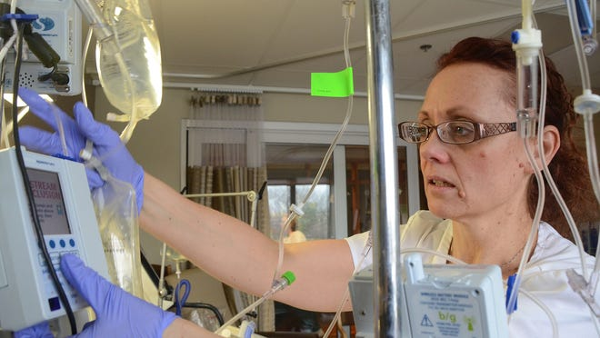 Brenda Young, RN, works in a patient's room in Bronson Battle Creek's critical care unit.