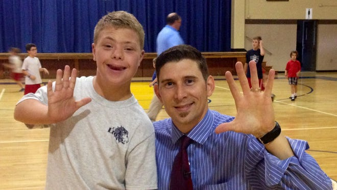 Davis Harkey, who has Down syndrome, inspired the fifth quarter of Christ  the King School's basketball games. He is seen with 10 News reporter Bobby Lewis.