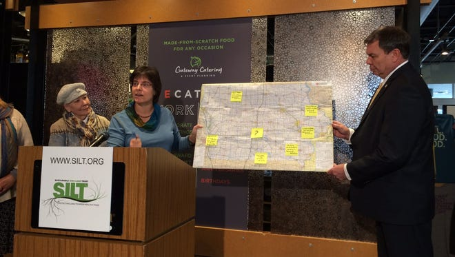 SILT President Suzan Erem and West Des Moines City Manager Tom Hadden hold a map highlighting SILT partners across Iowa. The nonprofit group dedicated to preserving farmland in and around Iowa's towns and cities held a kickoff event Wednesday at Gateway Market in Des Moines.