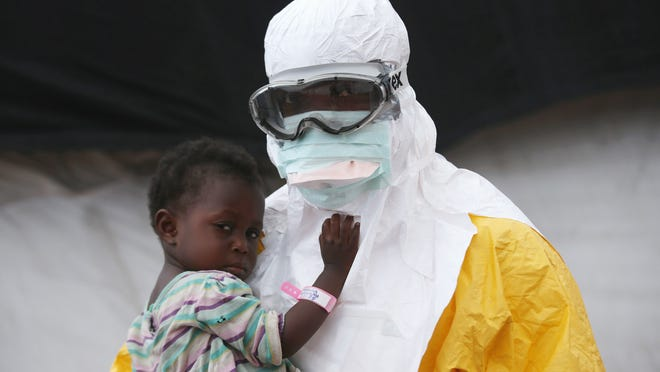 PAYNESVILLE, LIBERIA - OCTOBER 05:  A Doctors Without Borders (MSF), health worker in protective clothing holds a child suspected of having Ebola in the MSF treatment center on October 5, 2014 in Paynesville, Liberia. The girl and her mother, showing symptoms of the deadly disease, were awaiting test results for the virus. The Ebola epidemic has killed more than 3,400 people in West Africa, according to the World Health Organization.  (Photo by John Moore/Getty Images)