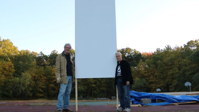 Black Bear Film Festival board members Max Brinson and Jerry Weinstock hold up one of nine panels that will form the drive-in screen for the festival in Akenac Park Oct. 16-17.