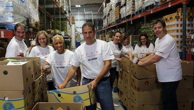 """Harris employees volunteer at the Second Harvest Food Bank in Melbourne as part of the company's """"120 Days of Service"""" challenge, which encourages employees to volunteer a minimum of 120 minutes of service over a 120-day period - totaling 40,000 volunteer hours.  The challenge is part of the company's new HEART community service initiative."""