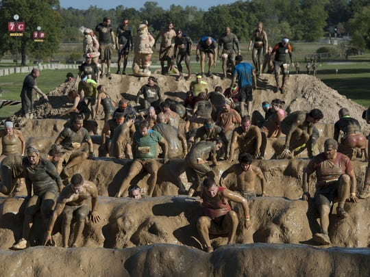 Participants take part in the Mud Mile 2.0 obstacle during the Tough Mudder at Michigan International Speedway.